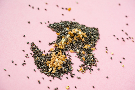 Healthy superfood:  flax seeds, chia seeds and hemp shelled seed on pink