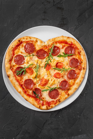 Heart shaped pizza with meat and vegetables. Food concept of romantic love for Valentines Day. Stock Photo