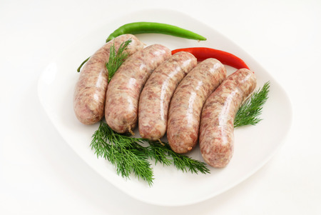 Raw sausages with herbs on the white plate