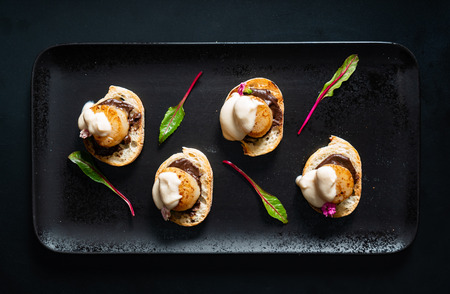 Scallop appetizers with sauce on the black Stock Photo