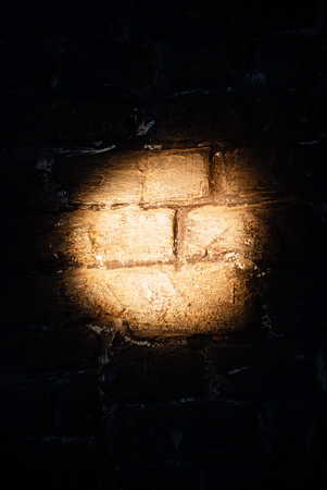 Dark red brick wall with spotlight