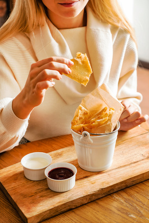 woman eating baked brushwood dessert with sauces