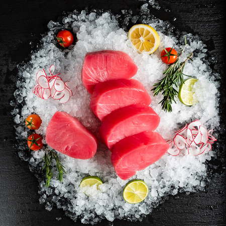 slice of tuna fish with lime, rosemary and cherry tomatoes on the ice Stok Fotoğraf