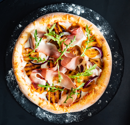 pizza with ham, persimmon and red onion
