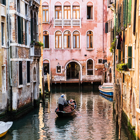 Venetian gondolier punting gondola through green canal waters of Venice Italy Banco de Imagens