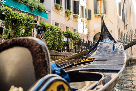 Venetian gondolier punting gondola through green canal waters of Venice Italy Stock Photo