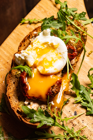 toast with dried tomatoes, poached egg and arugula leaves