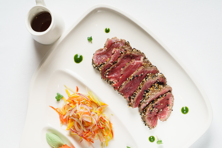 Appetizing slightly roasted tuna with salad and sauce, top view
