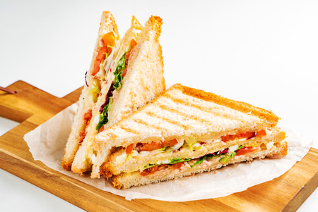 Sandwich with ham, cheese, tomatoes, lettuce, and toasted bread.