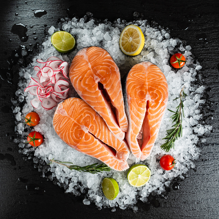 Slice of red fish salmon with lime, rosemary and  radish on the ice
