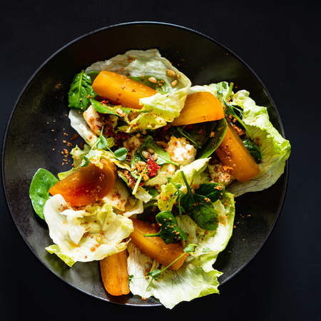 salad with persimmon on the black background 스톡 콘텐츠