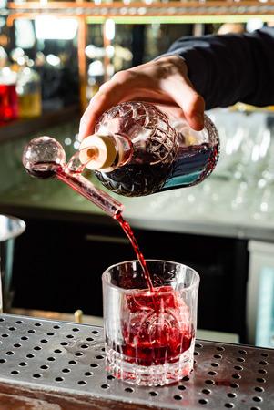 Expert barman making cocktail at nightclub