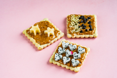 Delicious Toast with peanut butter on the pink background