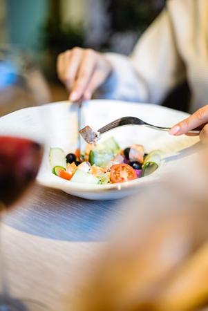 woman eating green healthy greek salad