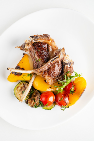 Modern French cuisine: Roasted Lamb neck & rack served with carrot, yellow curry and lamb sauce.