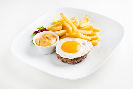 cutlet with egg and french fries Standard-Bild - 119982672