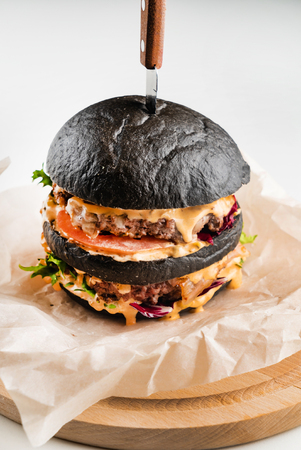 An appetizing black hamburger on the wooden background Stock Photo