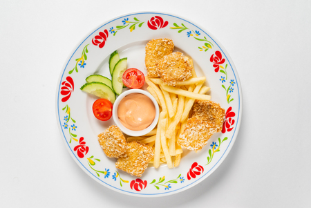 chicken nuggets with french fries and sauce on the white background
