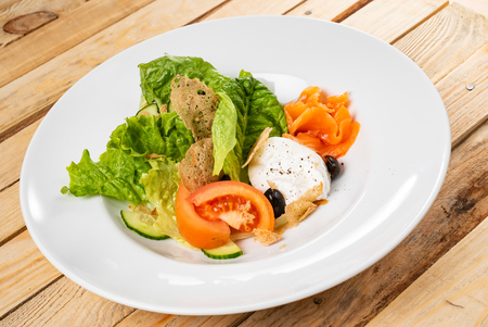 salad with mozzarella and salmon, wooden background