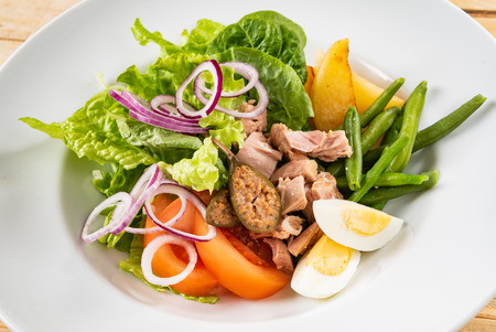 tuna salad with egg, tomatoes, red onions and green beans, wooden background