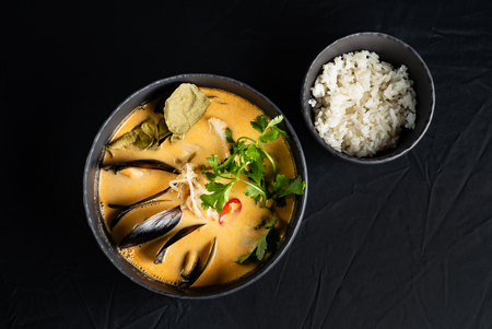 seafood soup and rice on the black background