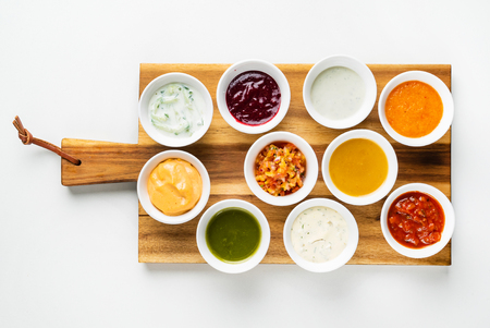 Bowls with sauces on wooden tray Banco de Imagens
