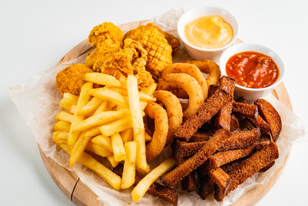 The beer plate with spicy chicken wings, calamari rings, fries onion rings, cheese balls, breaded, ketchup and mustard sauce Foto de archivo - 120822838