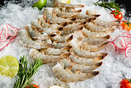 raw shrimps with lime and rosemary on the ice