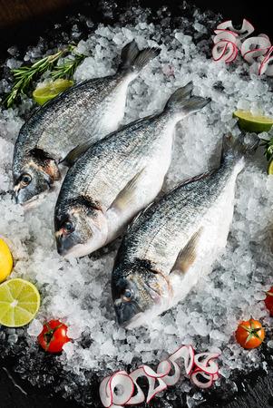 Fresh raw dorado fish and food ingredients on table