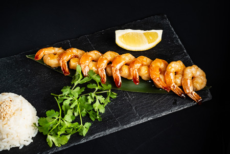 Grilled shrimp skewers. Seafood, shelfish. Shrimps Prawns skewers with herbs, garlic and lemon on black stone background,