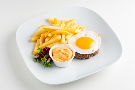 cutlet with egg and french fries Standard-Bild - 121349861