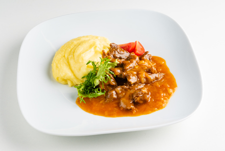 meat with mashed potato on the white plate