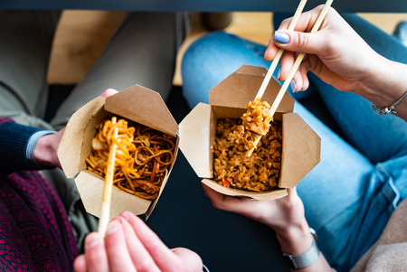 couple eating food packed in take-away box with chopsticks
