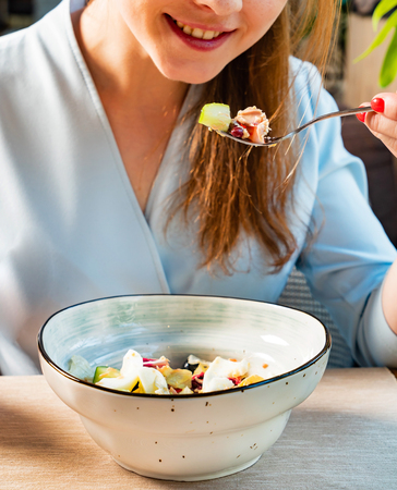 woman eating tuna salad with egg and olives Stock Photo