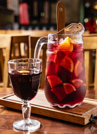 Red wine sangria or punch with fruits and ice in glasses and pincher.