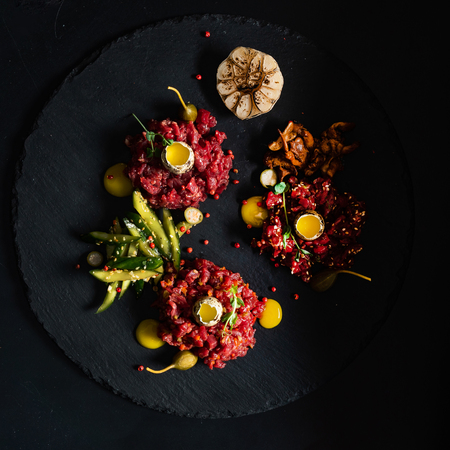beef tartare with egg yolk on black table
