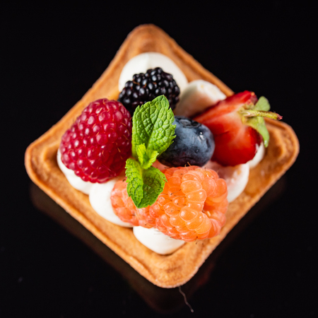 Fresh Fruit Tart with berries isolated on black background