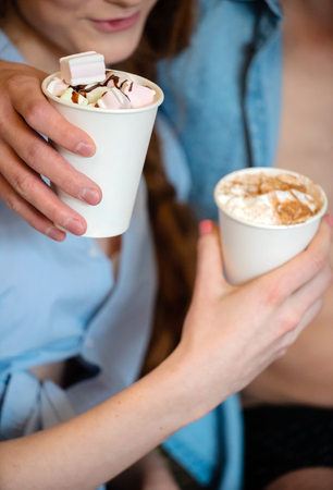 Happy young couple drinking coffee with marshmallow