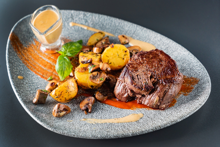 beef steak with sauce and baked potatoes