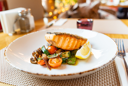 Salmon with roasted vegetables, dinner in the restaurant Фото со стока