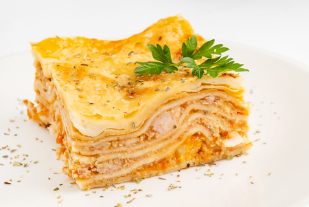 Meat lasagna on the white Imagens