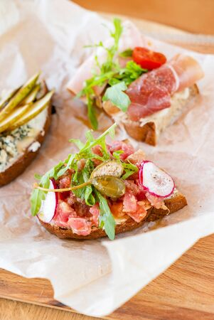 Different kinds of canape on the parchment Stock Photo