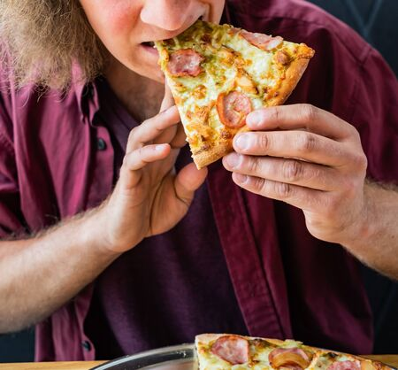 Man eating tasty Italian pizza
