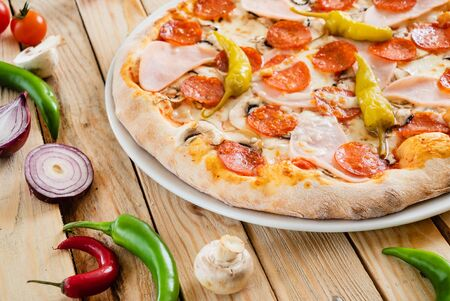 tasty pizza on the wooden background Stock Photo - 125077434