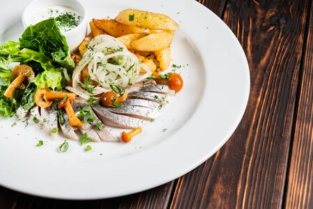 Herring with baked potato on the wooden