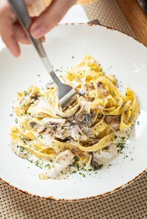woman eating Spaghetti Carbonara with chicken and cheese