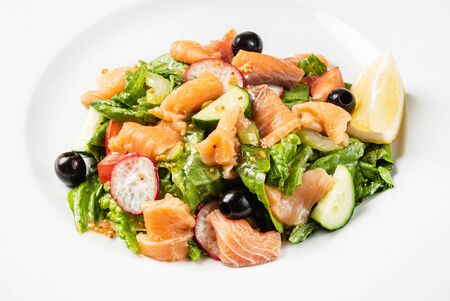 Salad with smoked salmon on the white plate