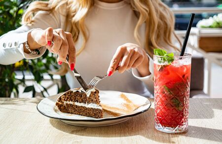woman eating carrot cake in the cafe