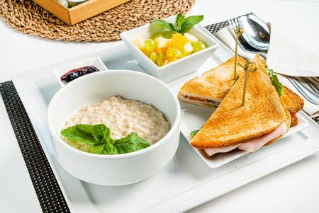 breakfast in the cafe with oatmeal and sandwich