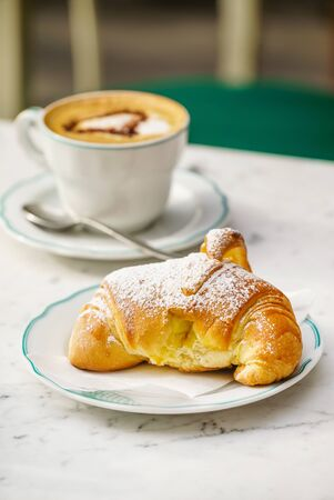 croissant and cappuccino in the cafe